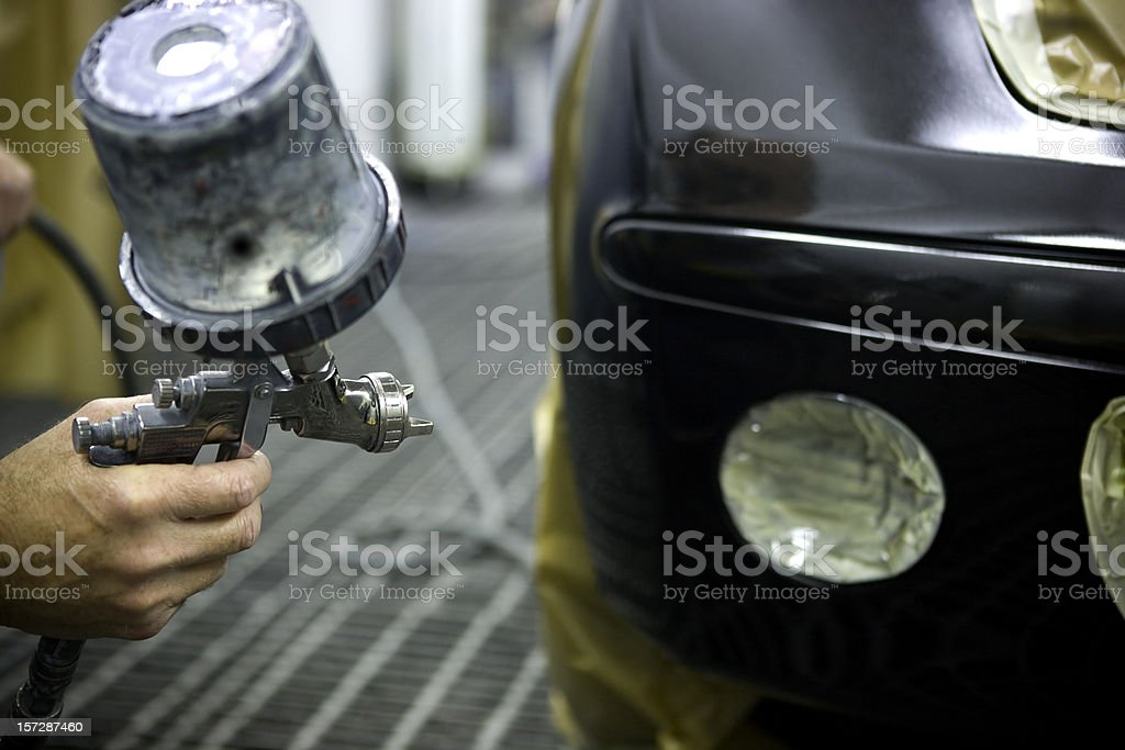 A man using a spray paint brush to paint a car stock photo