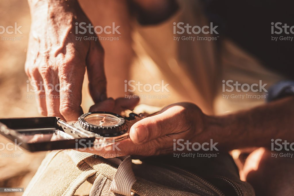 Man using compass for directions stock photo