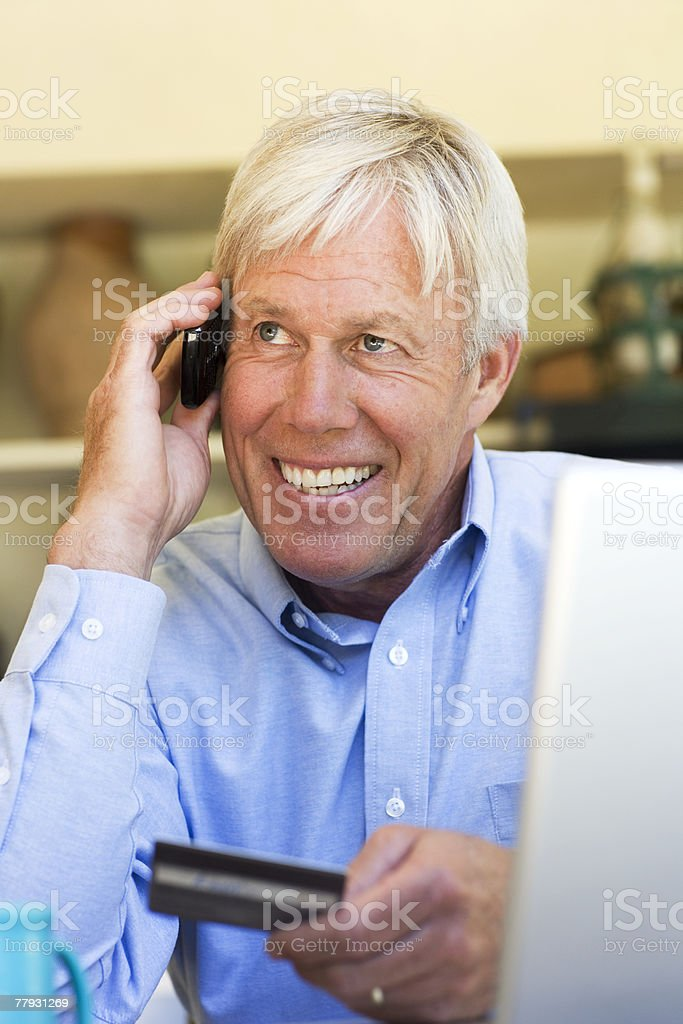 Man using credit card to shop over phone royalty-free stock photo