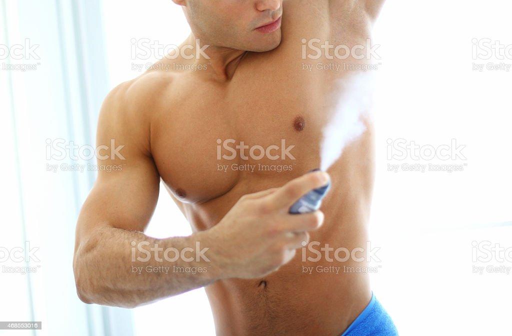 Man using deodorant spray. stock photo