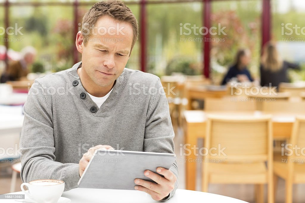 Man Using Digital Tablet At Cafe royalty-free stock photo
