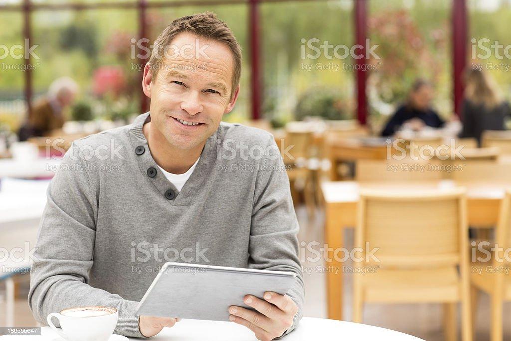 Man Using Digital Tablet At Cafe royalty-free stock photo