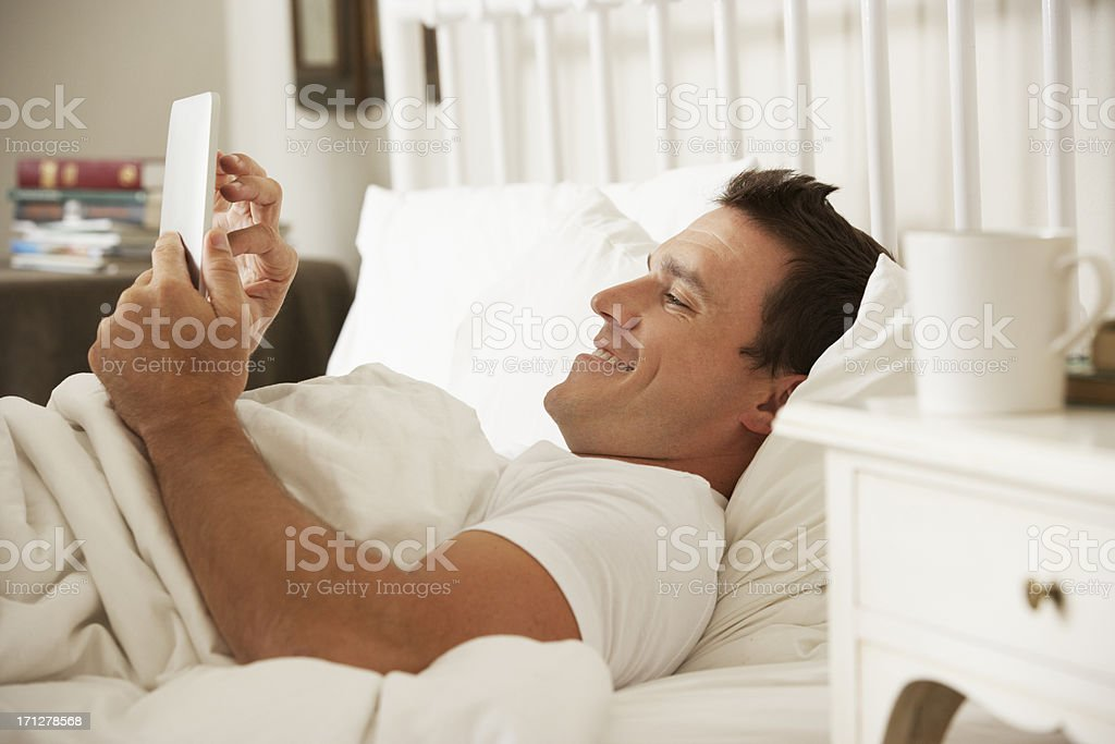 Man Using Digital Tablet In Bed At Home royalty-free stock photo