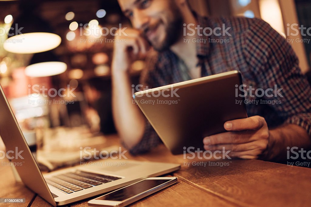 Man using digital tablet in cafe stock photo