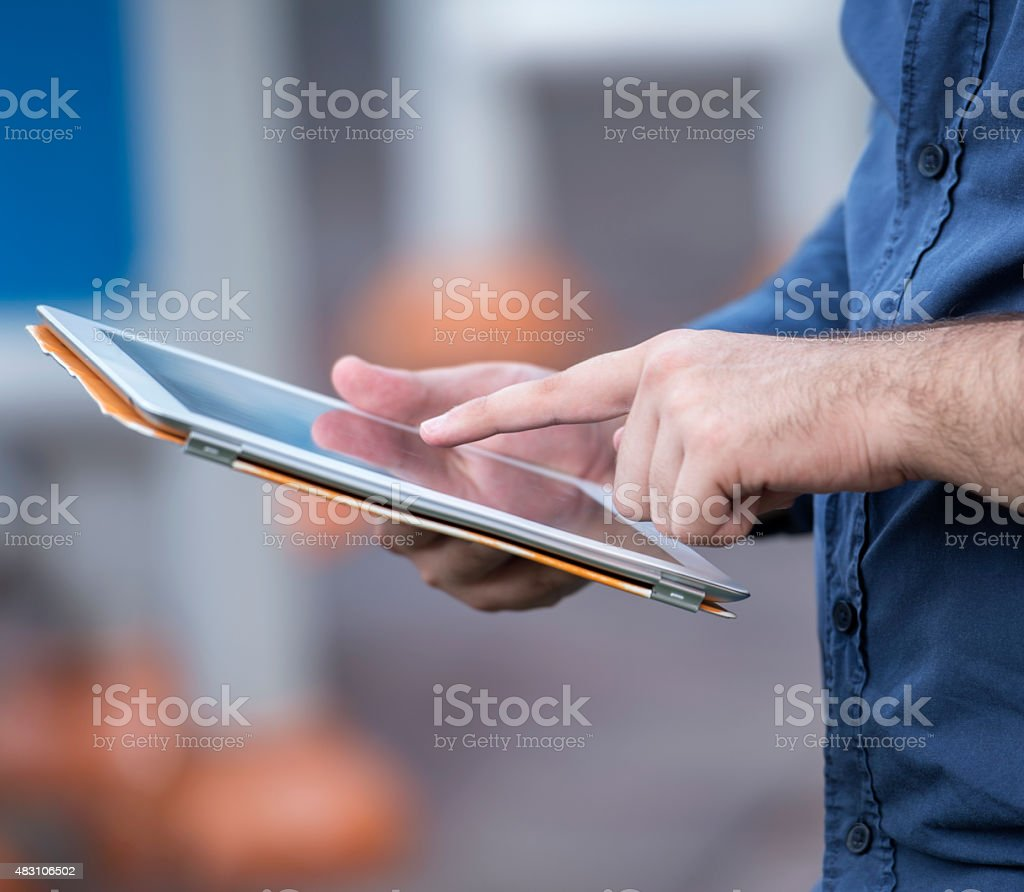 Man using digital tablet in park stock photo