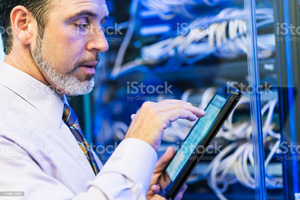 Man using digital tablet in server room stock photo