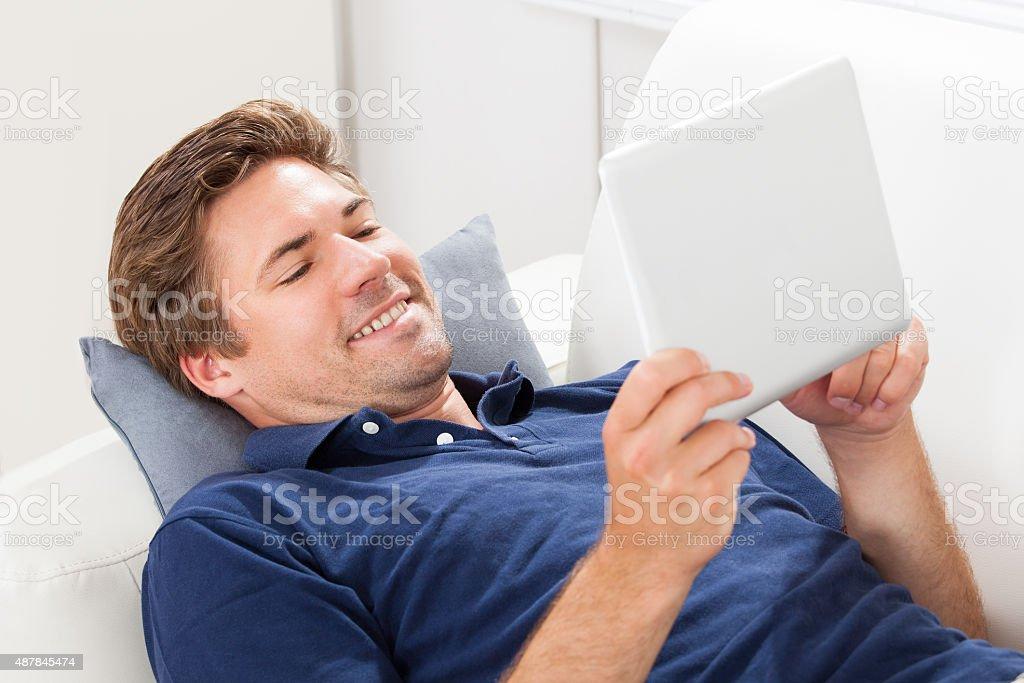 Hombre usando tableta Digital mientras están recostadas en SOFÁ - foto de stock