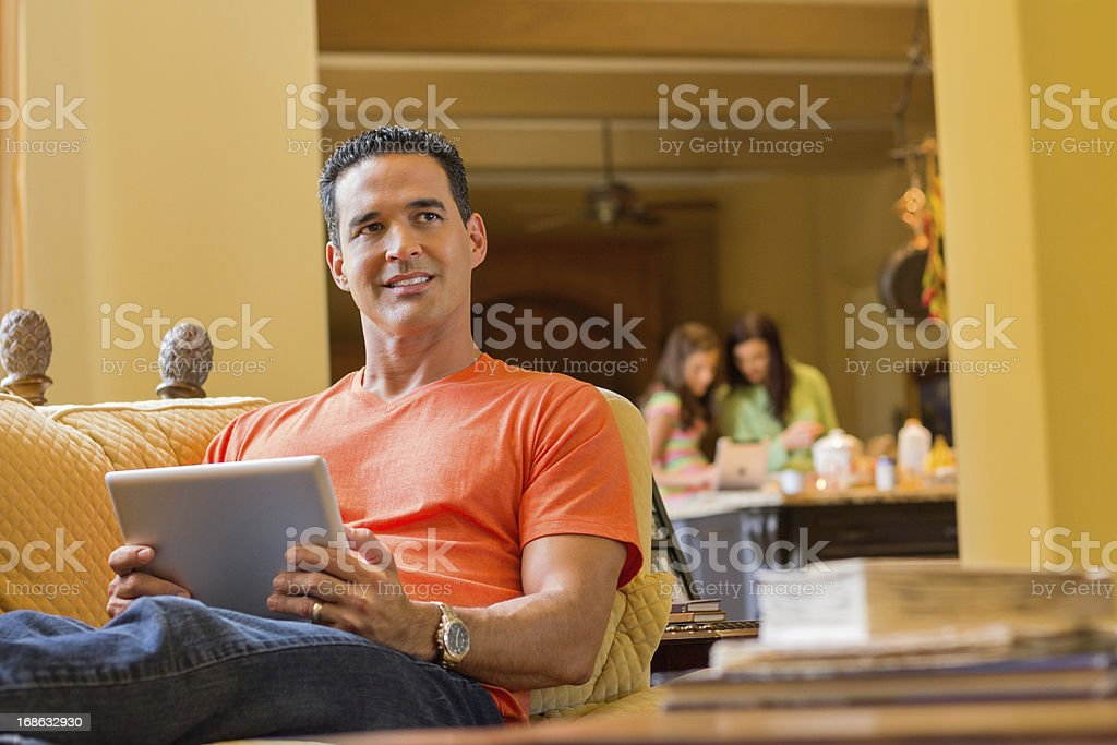 Man Using Digital Tablet With Family In Background royalty-free stock photo
