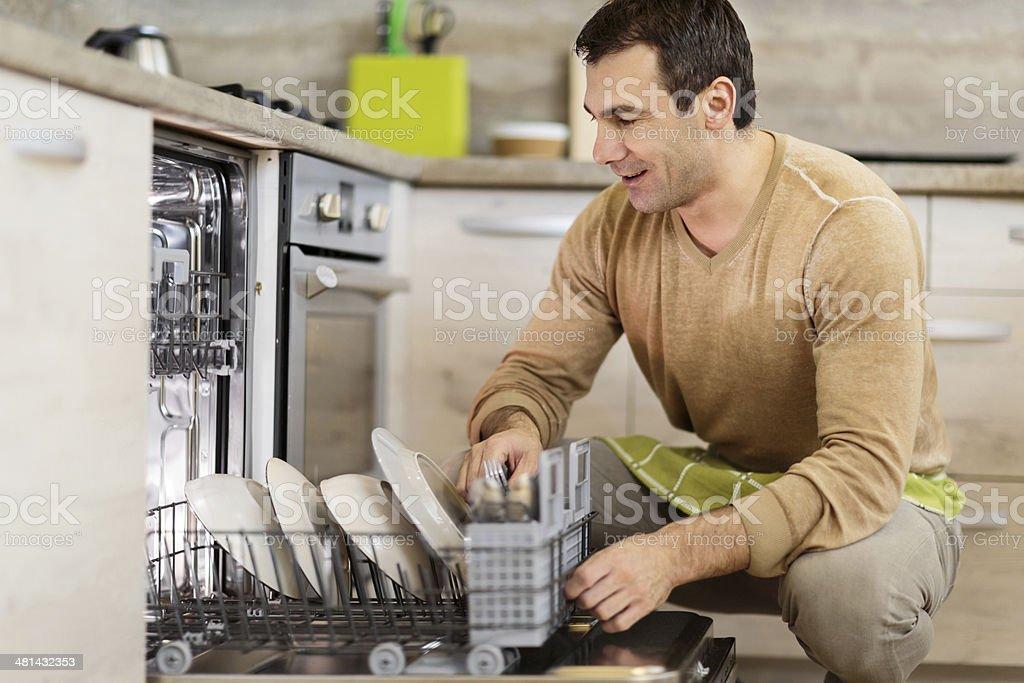 Man using dishwasher. stock photo