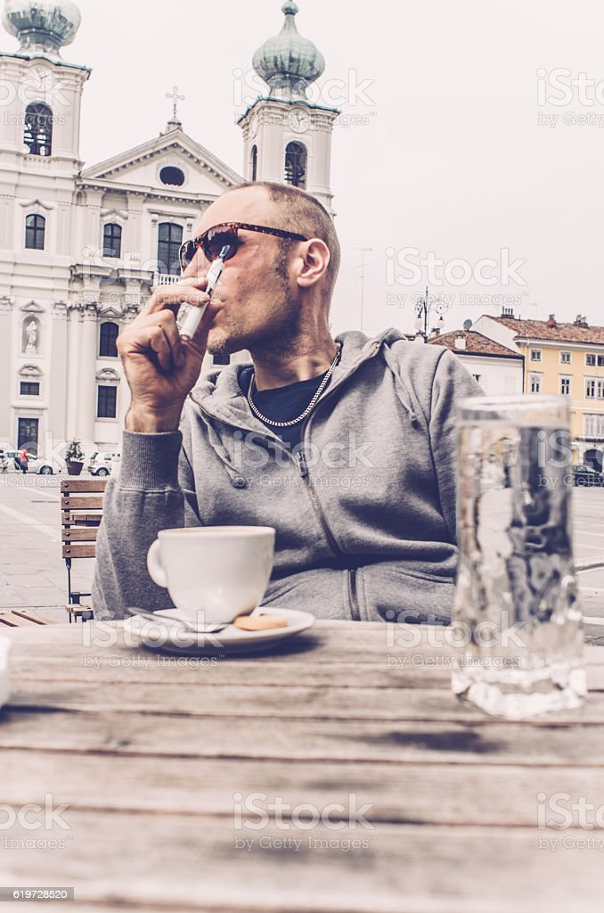 Man using electronic cigarette and drinking coffee, bar in Italy stock photo