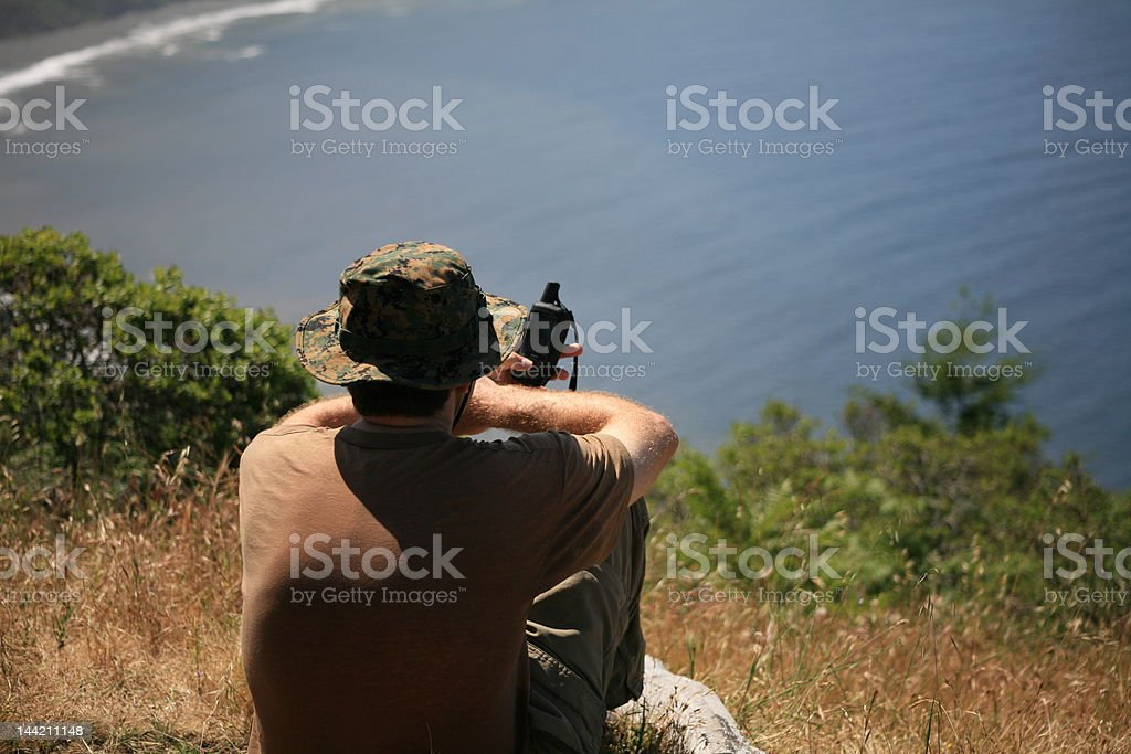 Man Using GPS on a Cliff over the Pacific royalty-free stock photo