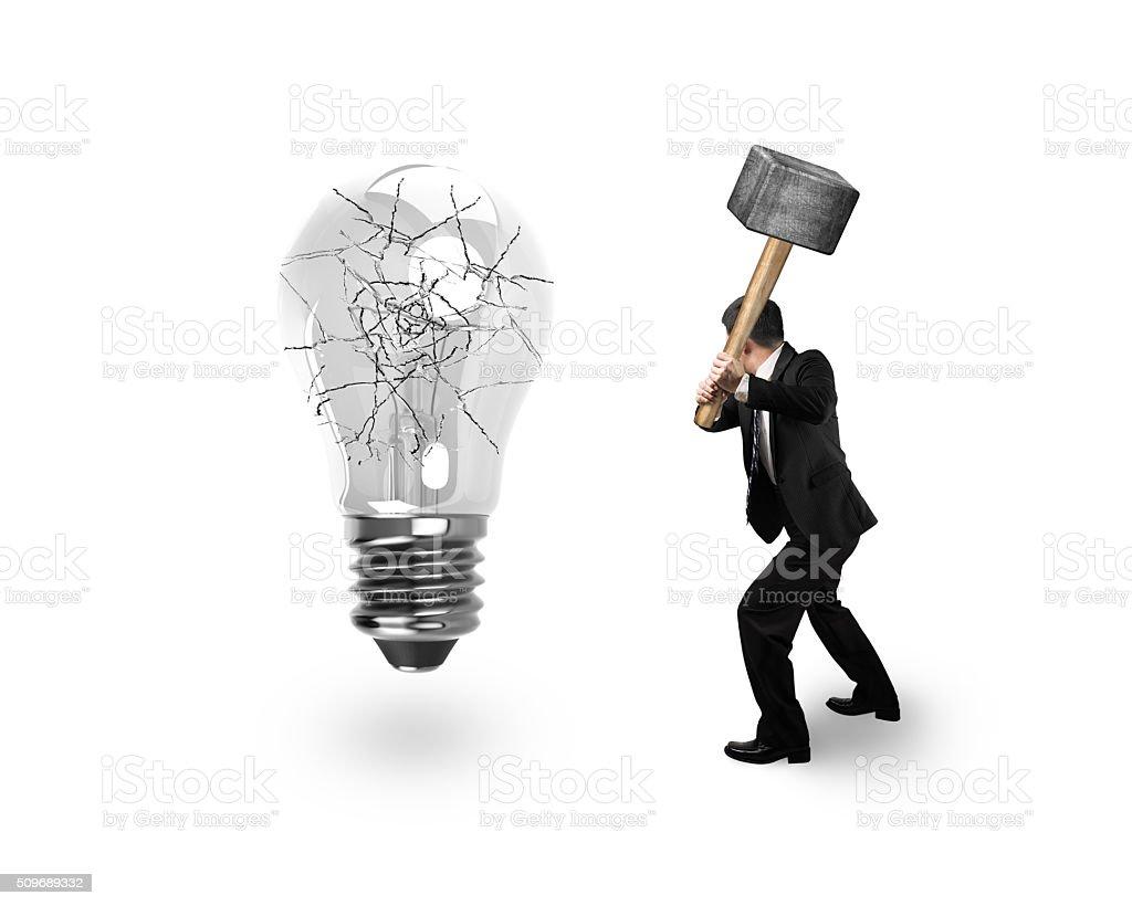 Man using hammer hitting light bulb with cracks stock photo