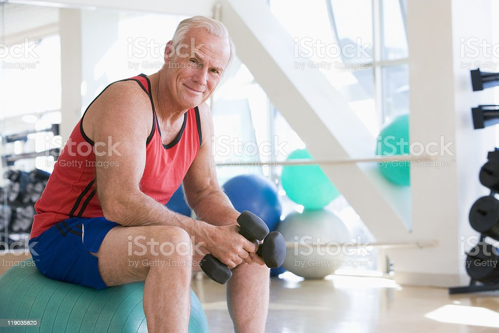 Man Using Hand Weights On Swiss Ball stock photo