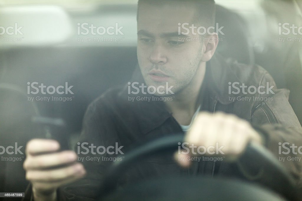 Man using his cellphone while driving stock photo