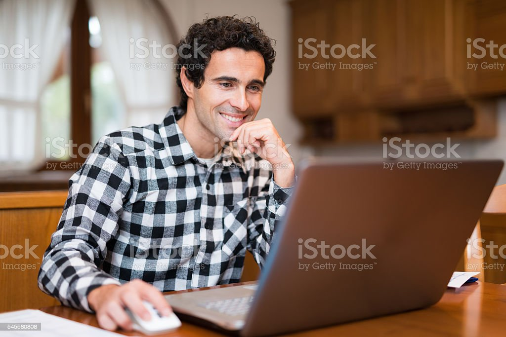 Man using his laptop at home stock photo