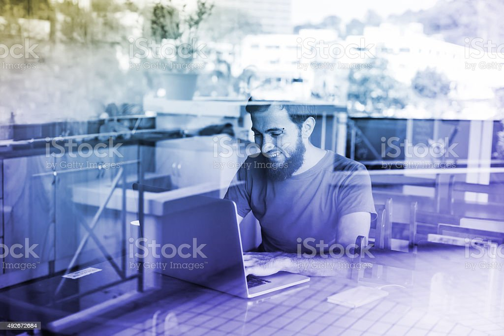man using his laptop - view through the window stock photo