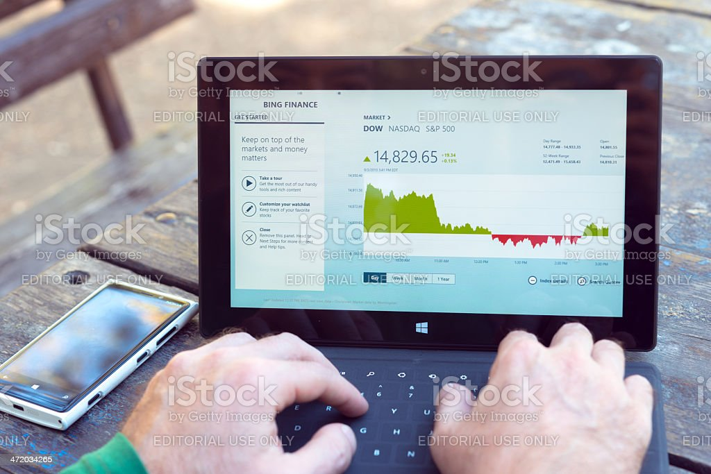 Man using his Microsoft Surface tablet at the park royalty-free stock photo