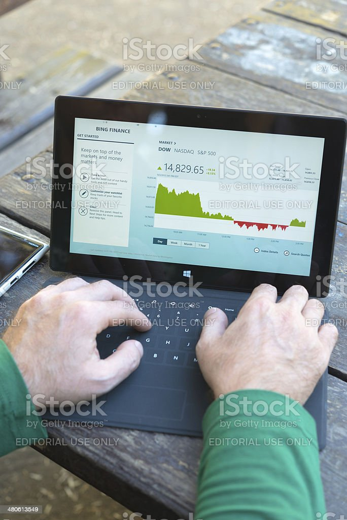 Man using his Microsoft Surface tablet at the park stock photo