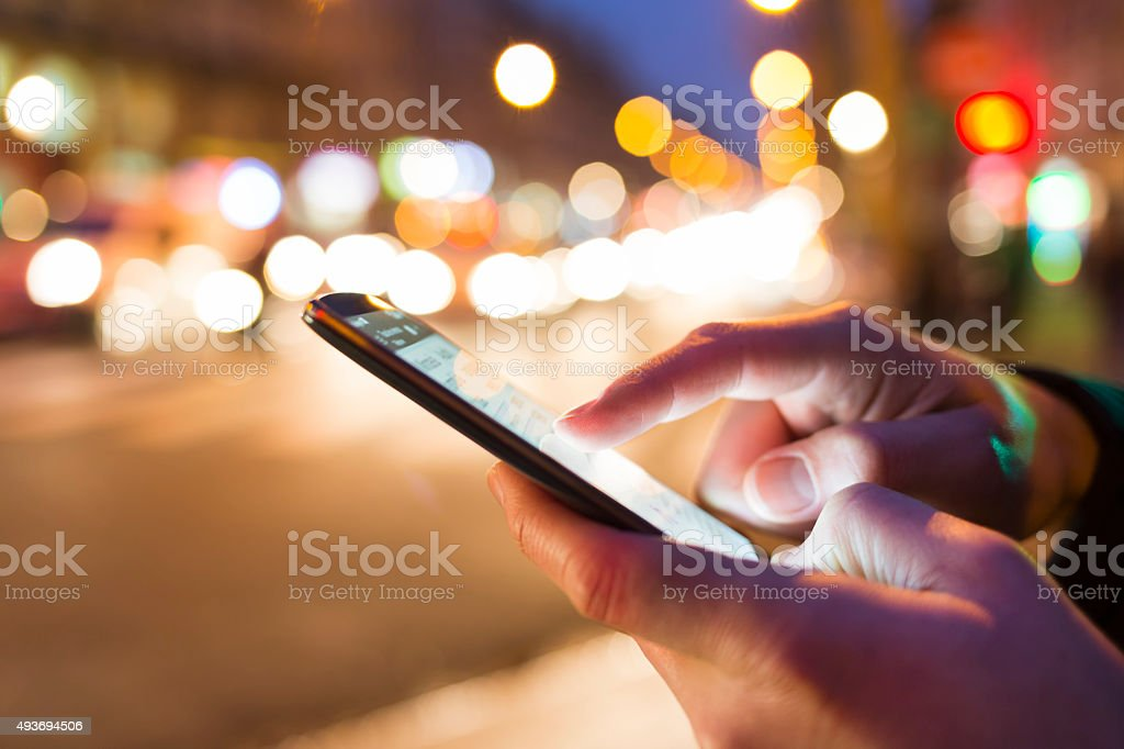 Man using his Mobile Phone in the street, bokeh stock photo