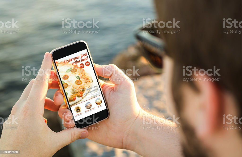 Man using his mobile phone  to order pizza online stock photo