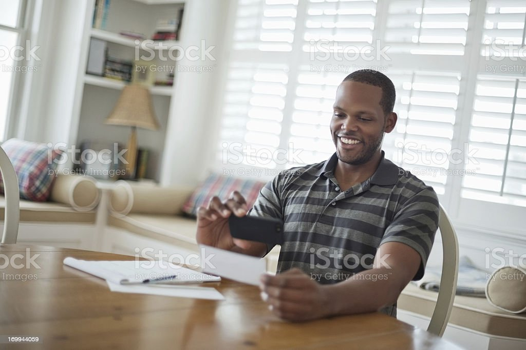 A man using his smartphone to deposit his check stock photo