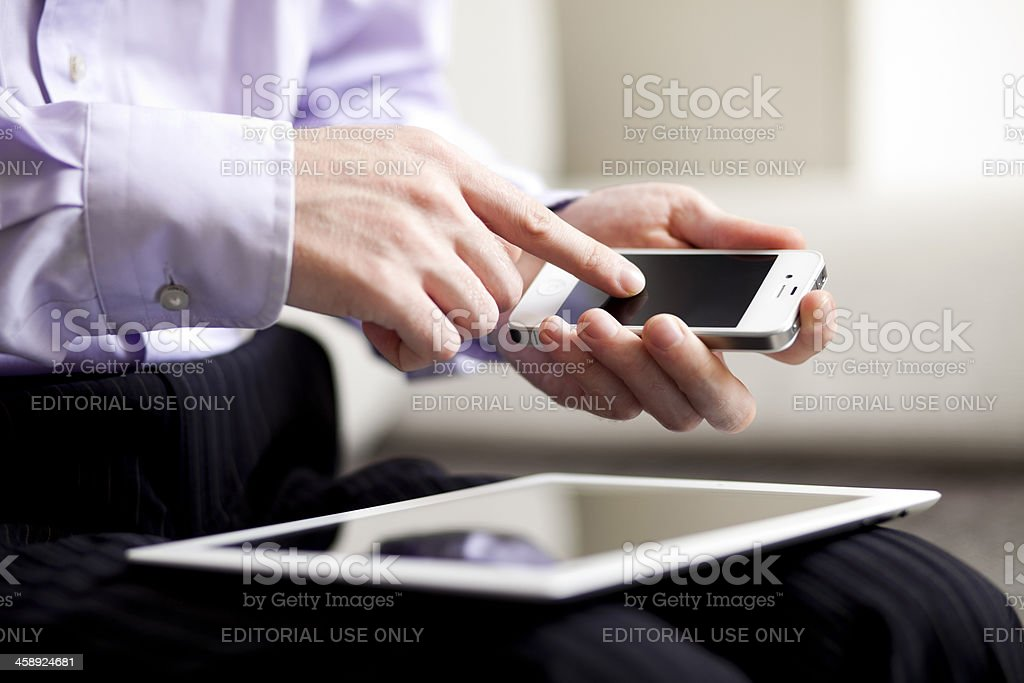Man using iPad and iPhone royalty-free stock photo