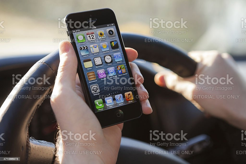 Man using iPhone 5 in car royalty-free stock photo