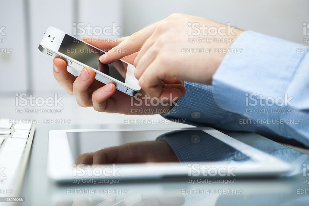Man Using iPhone and iPad royalty-free stock photo