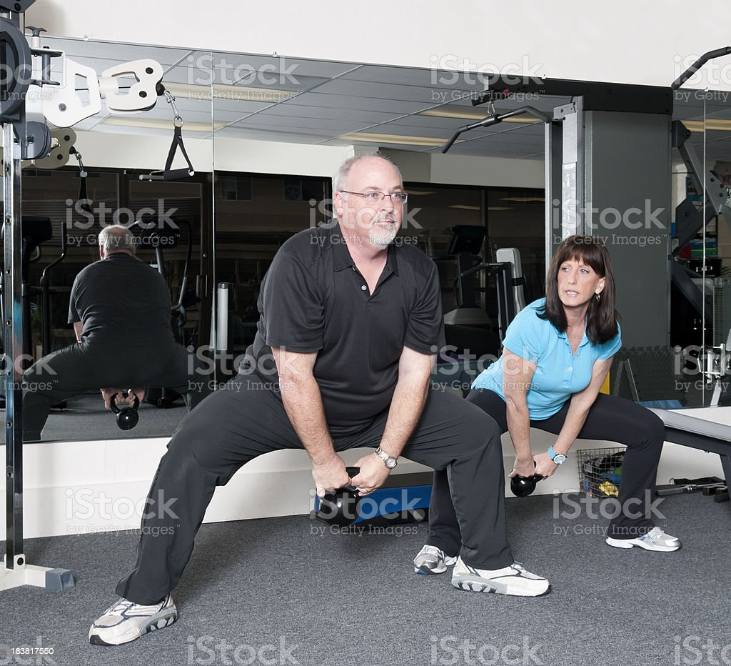 Man Using Kettlebells With Personal Trainer royalty-free stock photo