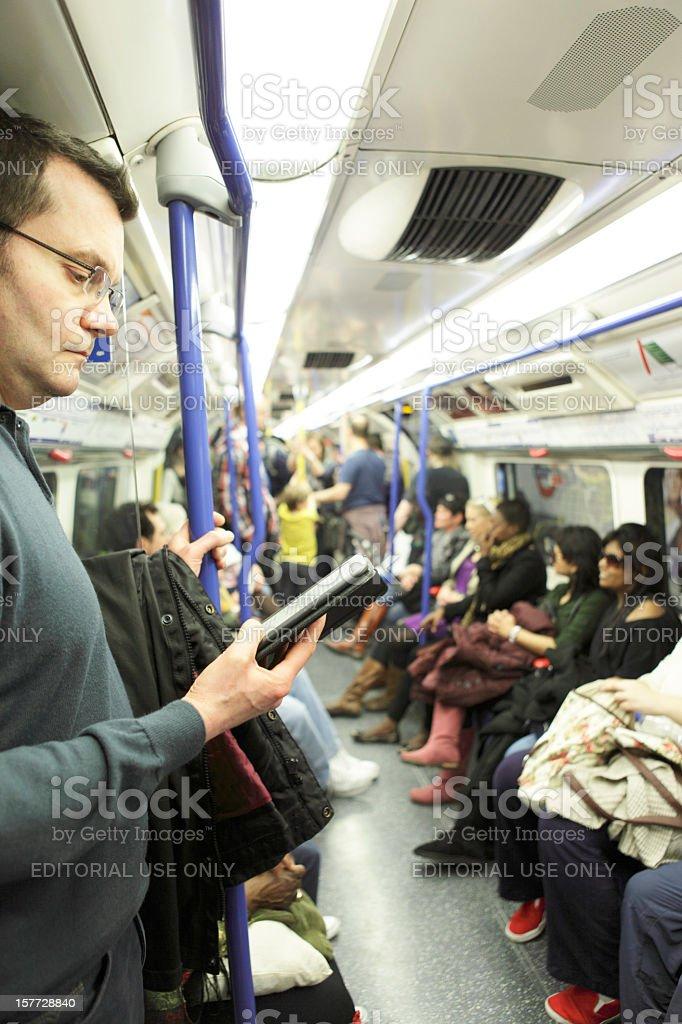 Man Using Kindle on London Tube Underground Train stock photo