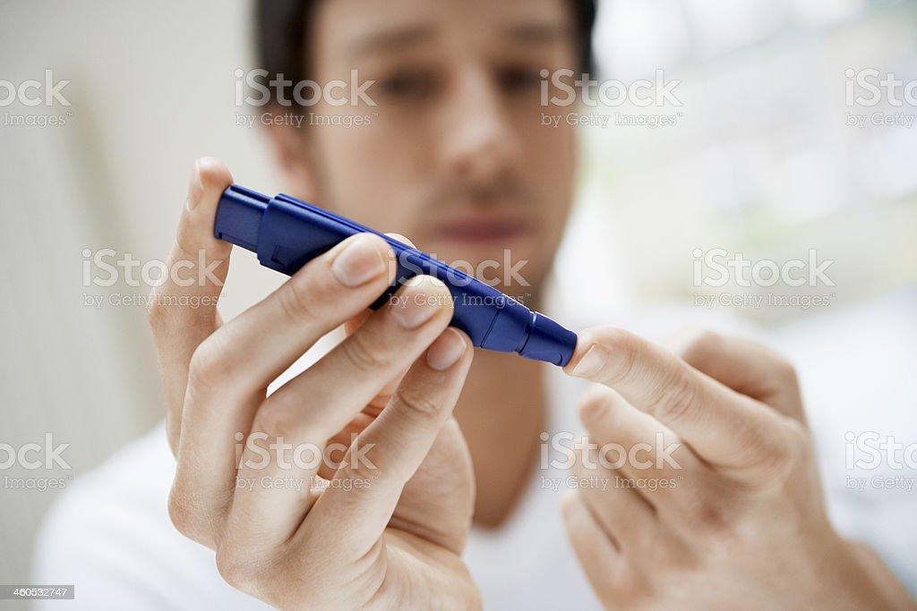 Man Using Lancelet On Finger In Bathroom stock photo