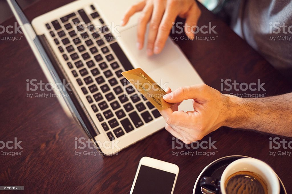 Man using lap top for credit card payments stock photo