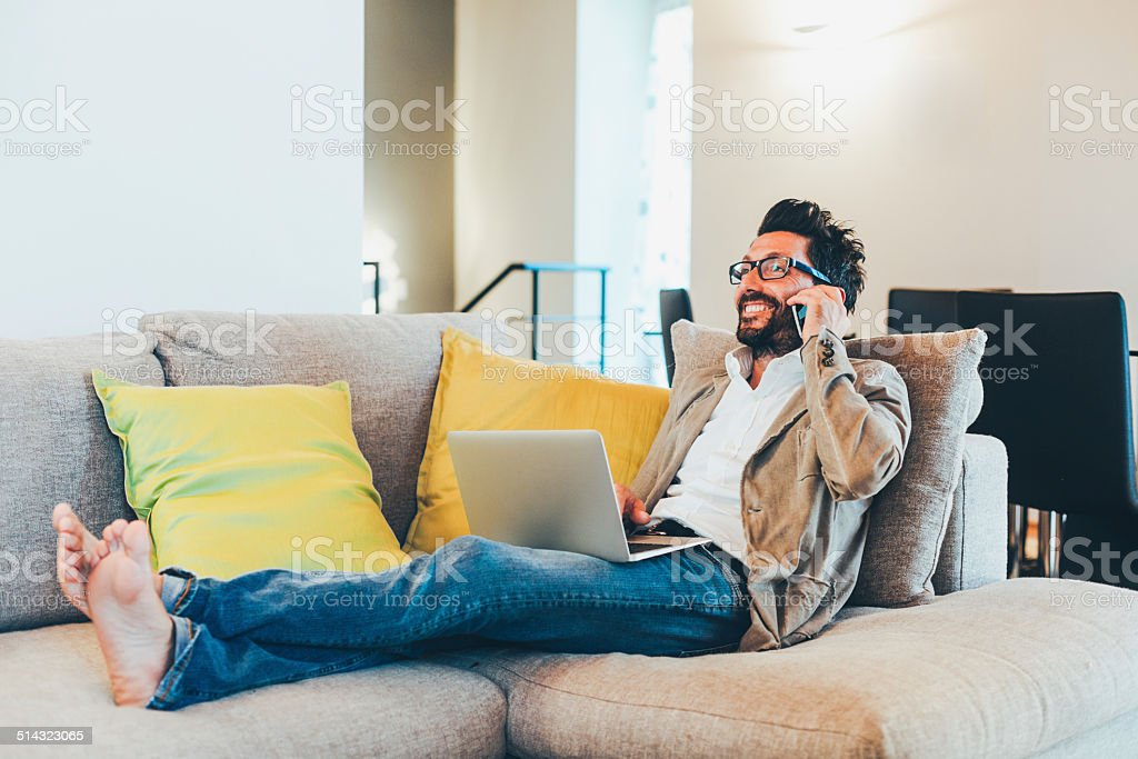 Man using laptop and smart phone on sofa stock photo