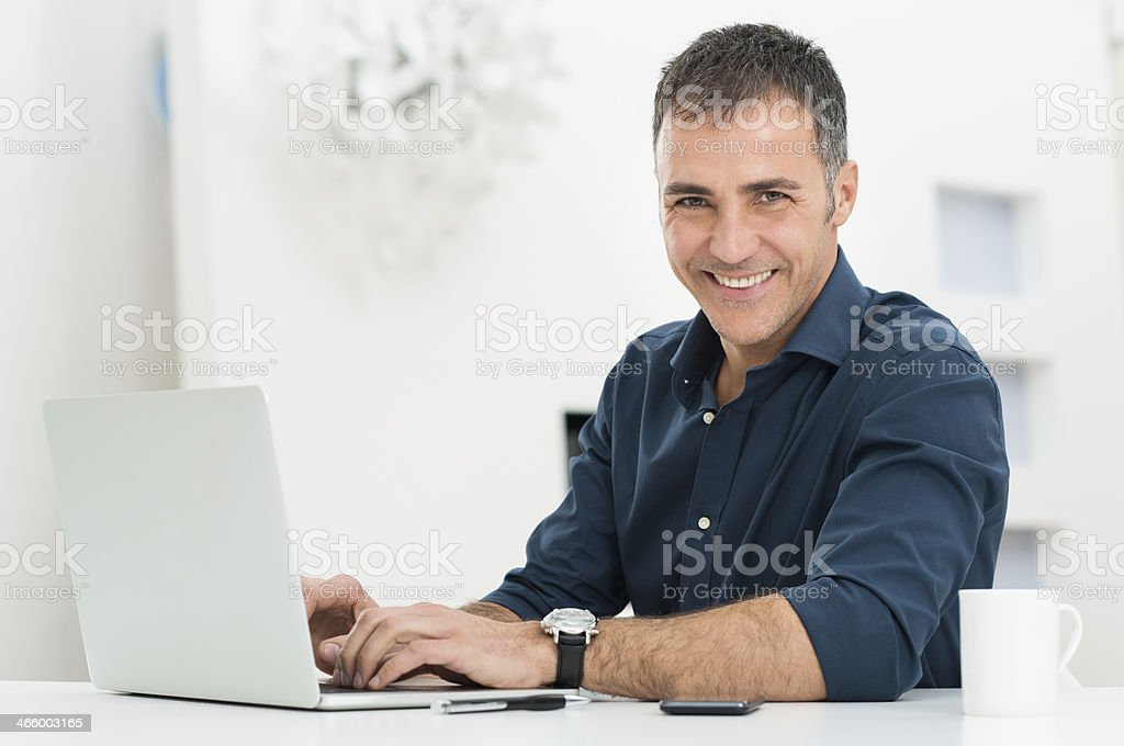 Man Using Laptop At Desk stock photo