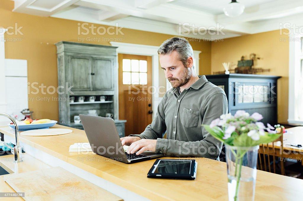 Man using laptop at home stock photo