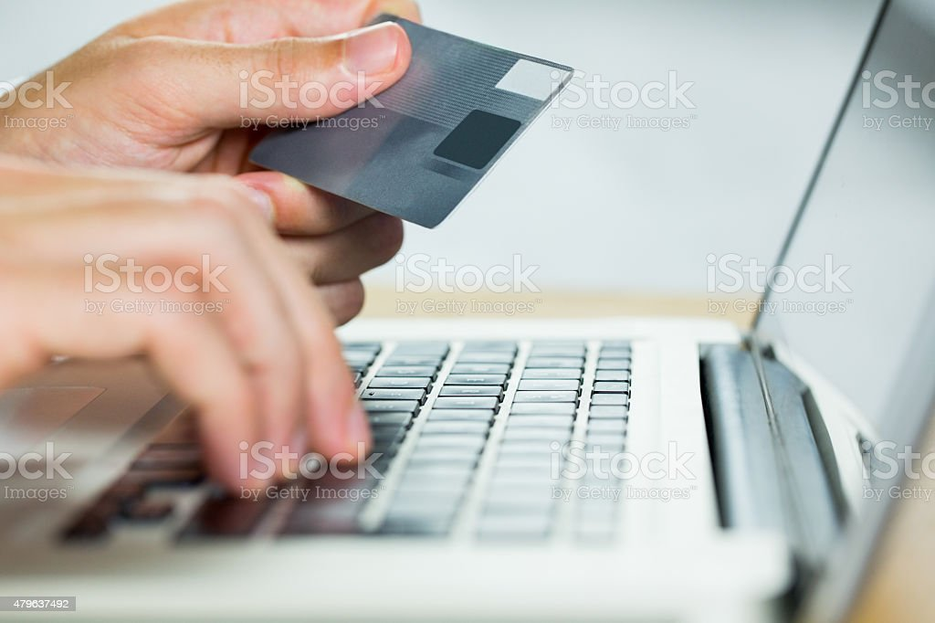 Man using laptop for online shopping stock photo