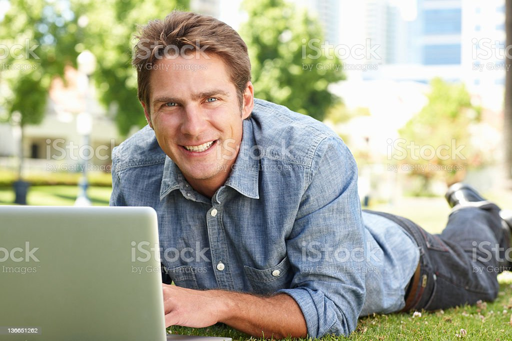 Man using laptop in city park royalty-free stock photo
