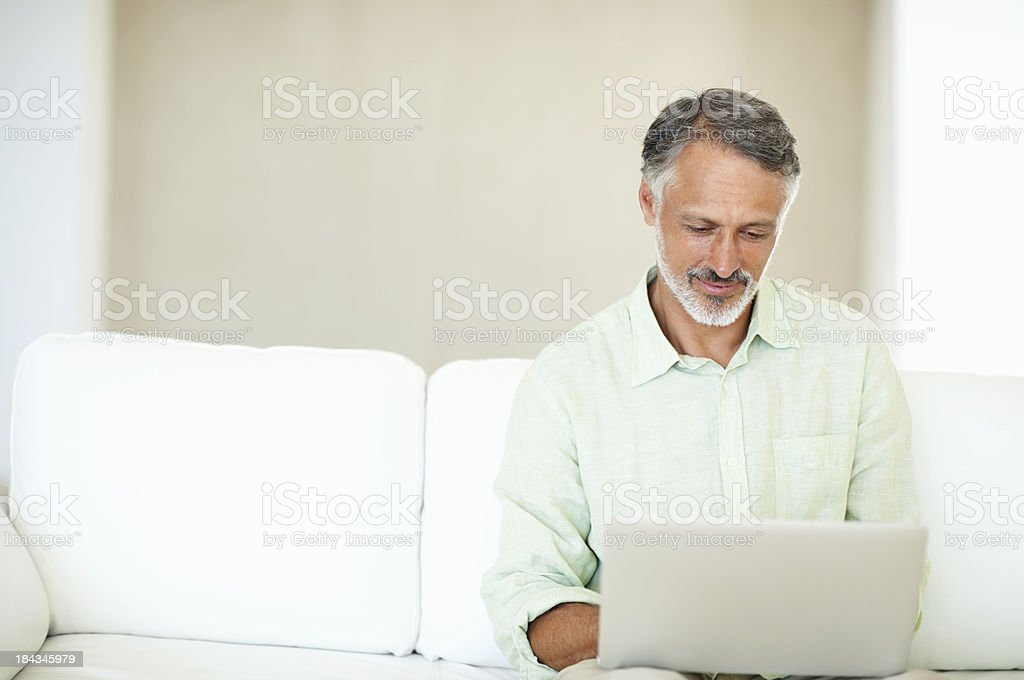 Man using laptop on a couch royalty-free stock photo