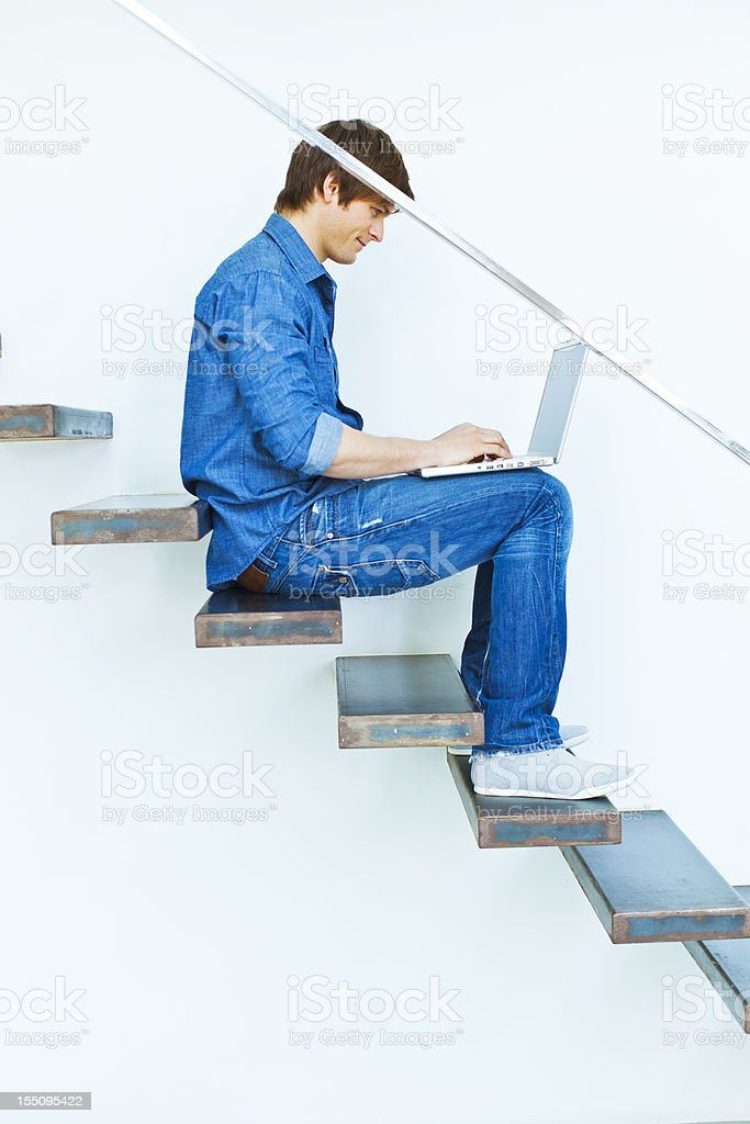Man using laptop on a modern staircase royalty-free stock photo