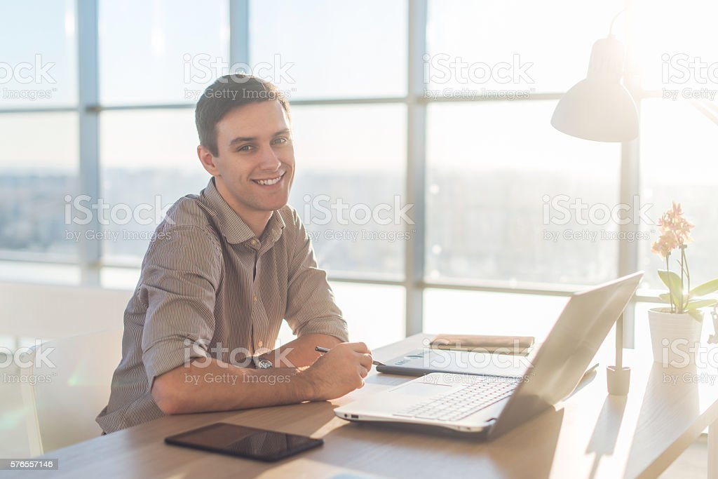 Man using laptop on his workplace. sitting, smiling, looking at stock photo