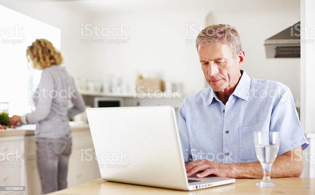 Man using laptop while woman cooking in the kitchen royalty-free stock photo