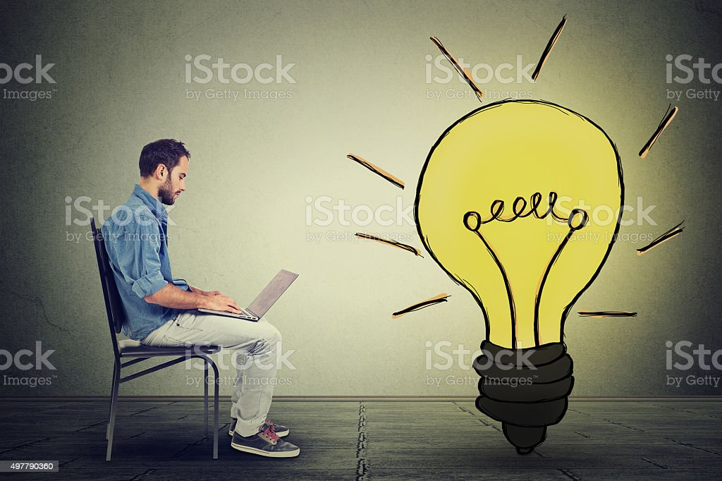man using laptop with light bulb on gray wall background stock photo