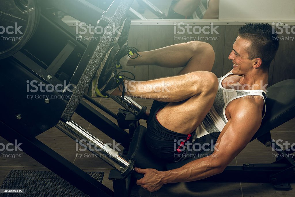 Man using leg press in gym stock photo
