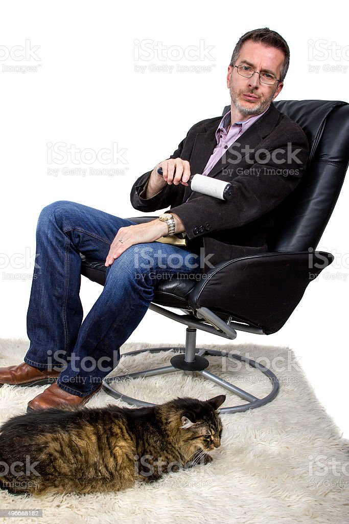Man Using Lint Roller To Clean Cat Fur stock photo