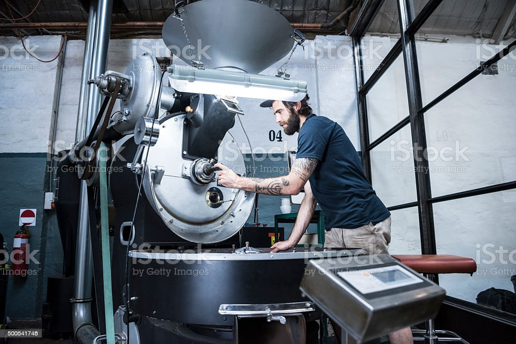 Man using machinery in coffee roasting warehouse stock photo