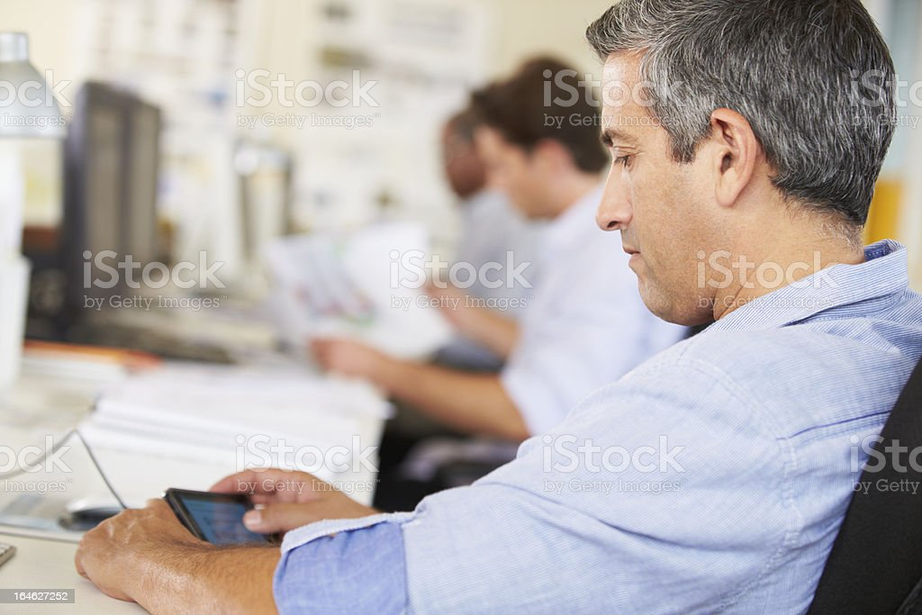 Man Using Mobile Phone At Desk In Creative Office royalty-free stock photo
