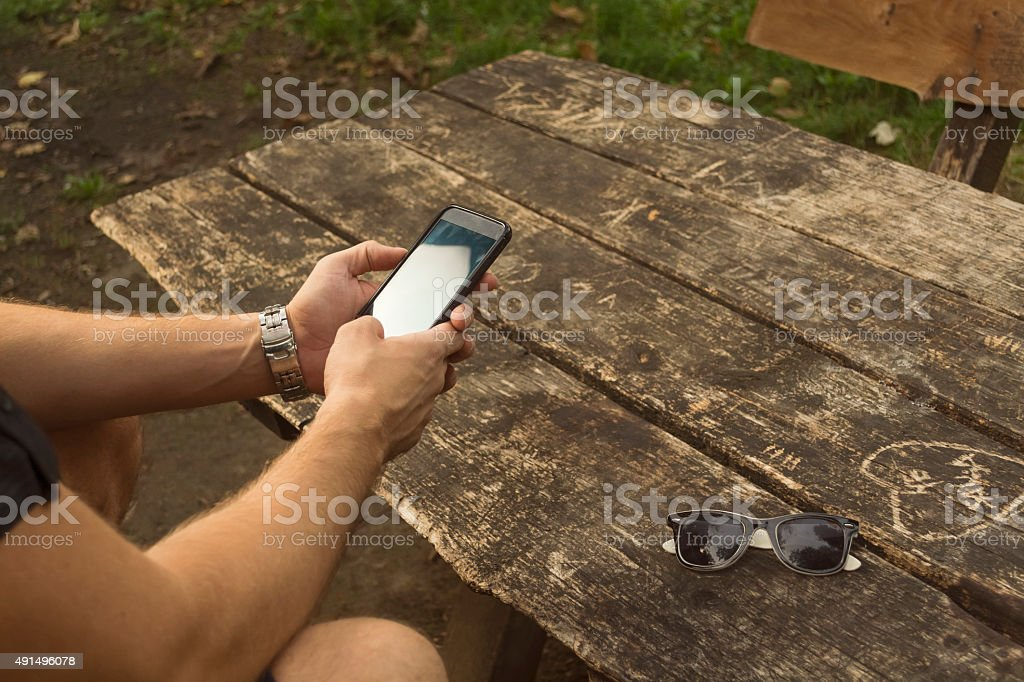 Man Using Mobile Phone in a park royalty-free stock photo