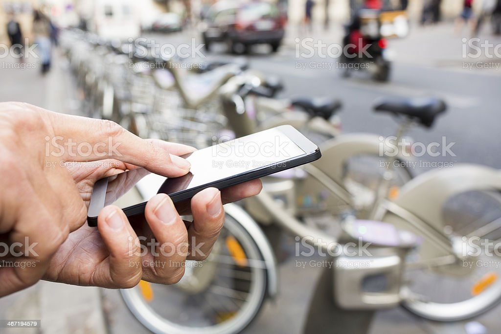 Man using mobile phone in front of Velib Station, Paris stock photo