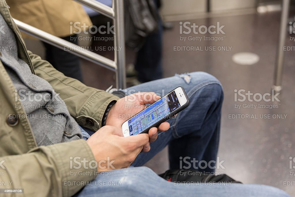 Man Using Mobile Phone in Subway Train, NYC stock photo