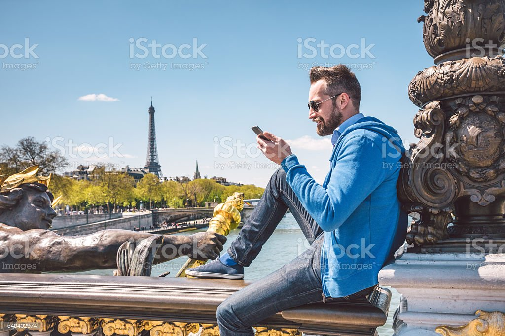 man using mobile phone on Pont Alexandre bridge in Paris stock photo